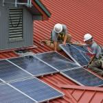 A photo of an installer putting up solar panels on a stable block in West Sussex, UK